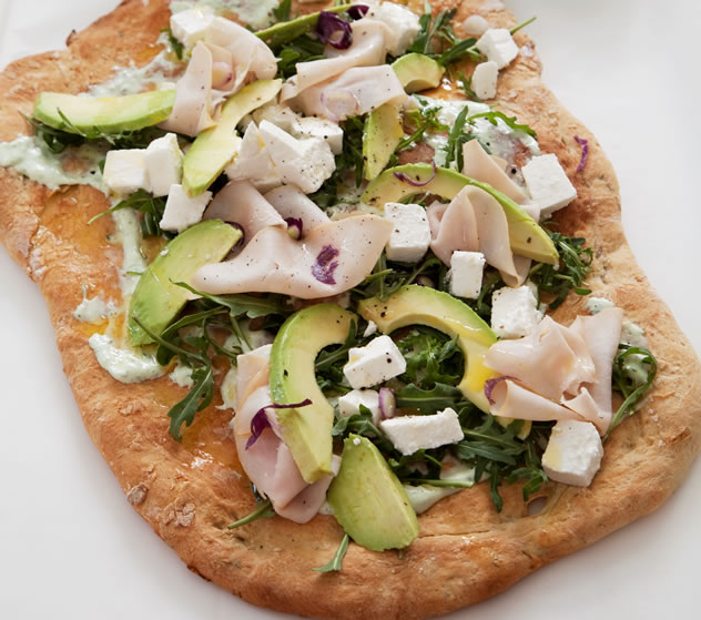 Avocado-topped flatbread with turkey, rocket and feta cheese.