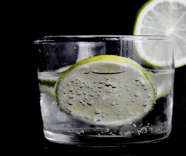 A glass of water with a slice of lemon.