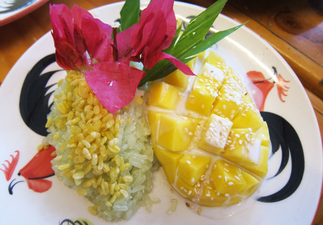 Mango sticky rice topped with a sprinkling of sesame seeds and toasted mung beans.
