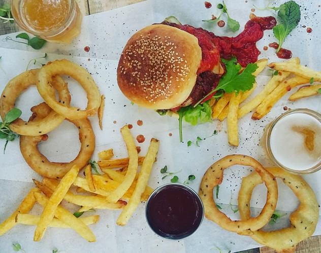 A burger onion rings and chips at Capital Craft