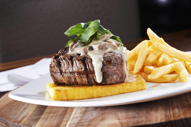 A steak topped with sauce along chips at Piatto. Photo courtesy of the restaurant.