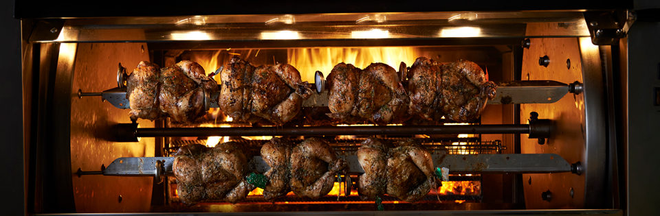 chicken roasted in front of a fire at Rosto