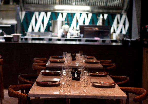 The marble-topped dining tables and open kitchen at ASH. Photo by Matthew Ibbotson.