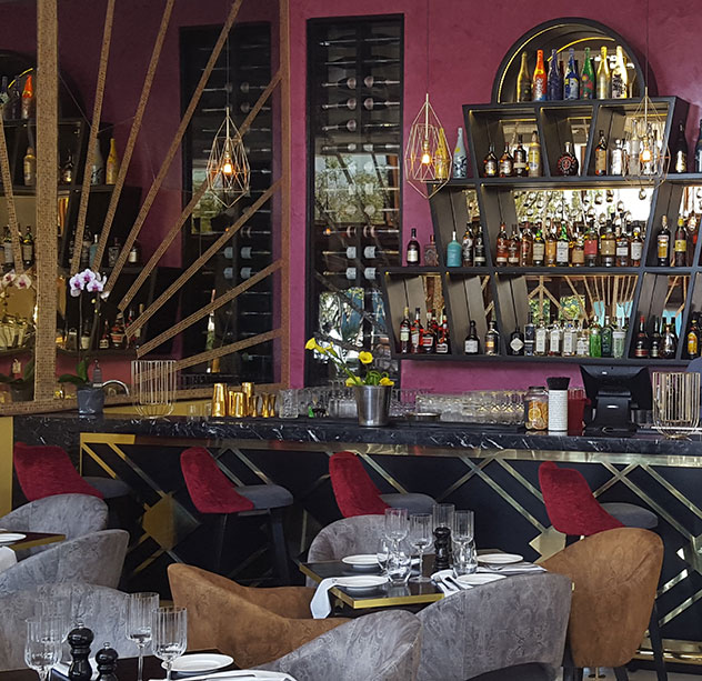 Plush red seats add a pop of colour to the dark bar area. Photo supplied.