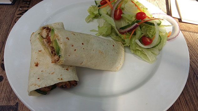The chicken wrap contains hummus, cottage cheese, tomato, lettuce and cucumber, accompanied by a Greek salad or chips. Photo by Thando Ndabezitha.