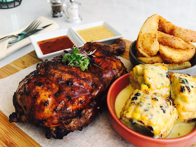 Half Price Rotisserie Chicken with buttered corn and spicy potato wedges at Strolla. Photo supplied.