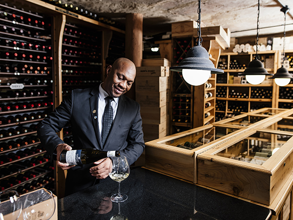 Sommelier Moses Magwaza pouring wine in one of the biggest wine cellars in South Africa.