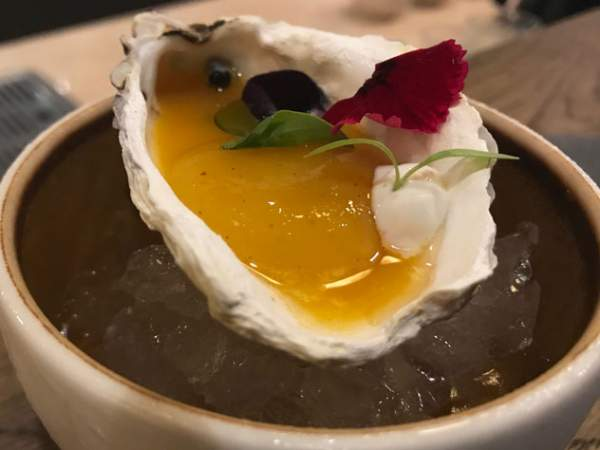 The mango-and-passion-fruit coulis served in an oyster shell